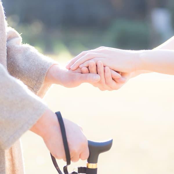 女性と年配の女性が手を取り合っている写真